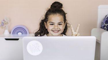 Op deze foto zie je een klein meisje achter een labtop