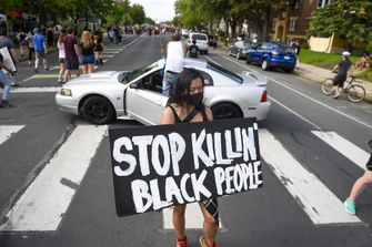 Op de foto is te zien hoe er wordt geprotesteerd na een arrestatie van een zwarte man.
