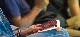 Op deze foto zie je iemand die zijn paspoort en vliegtickets vasthoud.