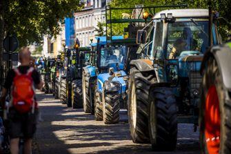 Een foto van een lange rij tractoren op weg naar een protest