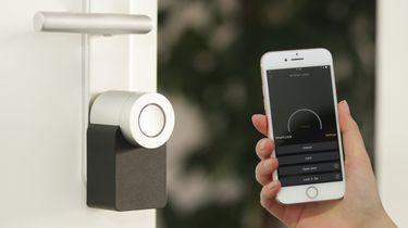 Een foto van een deurslot en een smartphone die het slot bedient