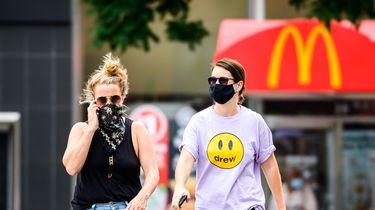 Een foto van twee dames met een mondkapje voor een McDonald's-vestiging