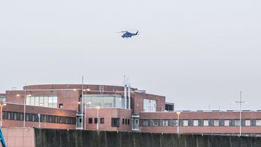 Op deze foto is een helikopter te zien die boven de gevangenis in Zutphen vliegt.