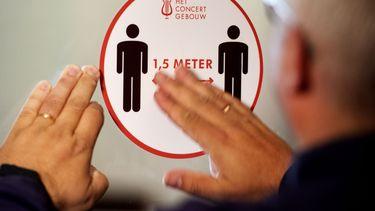 Een foto van een sticker waarbij de 1,5 metermaatregel wordt vermeld