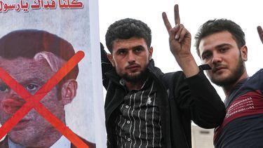Op deze foto zijn twee mannen te zien met een bord waarop president Macron is afgebeeld met een varkensneus. Er staat een rood kruis over zijn gezicht.