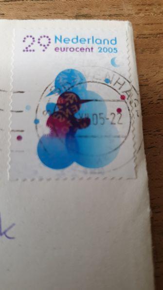 Een ingezoomde foto van een blauwe postzegel met het jaartal 2005 erop
