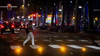 Voetgangers steken de Coolsingel over via een interactief zebrapad, waarbij lampen in het wegdek oplichten als er iemand gaat oversteken. Foto: ANP | Robin van Lonkhuijsen