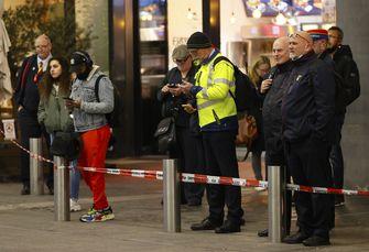 Een foto van mensen die gelaten wachten bij het afgesloten Utrecht Centraal