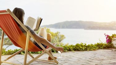 Een foto van een vrouw die in een oranje strandstoel een boek leest op een terras aan een meer. Ze heeft een glas wijn in haar hand.