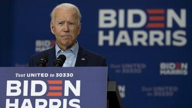 Op deze foto is presidentskandidaat Joe Biden te zien. Hij staat achter een bordje met 'Biden Harris'.