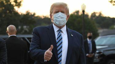 Donald Trump met mondkapje op, hij steekt een duim omhoog.