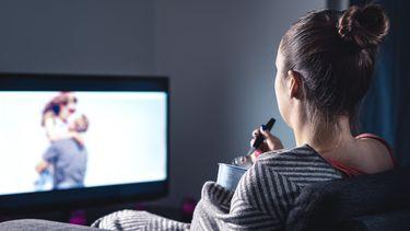 Op deze foto zie je een vrouw een film kijken