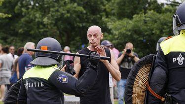 Op deze foto zie je demonstranten die de confrontatie zoeken met de politie in het centrum van Den Haag. Politie is voorbereid op eventuele rellen dit weekend.