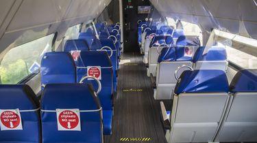 Een foto van een lege trein waar er bordjes op de stoelen aangeven of het wel of niet een zitplaats is.