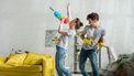 Een foto van een man die samen het huishouden doen en hun schoonmaakattributen gebruiken als muziekinstrumenten