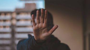 man steekt hand op om nee te zeggen