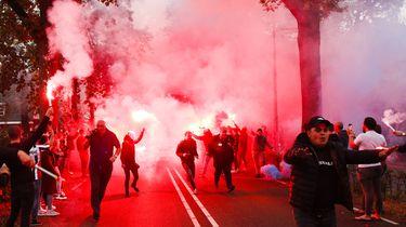 Een foto van supporters van Willem II die de spelersbus onthalen