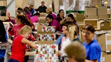 Medewerkers pakken kerstpakketten in bij de Makro.