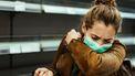 Een foto van een vrouw in een bruin jasje die met mondkapje op in haar ellenboog niest