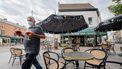 Een foto van een horecaman met mondkapje op een terras in Antwerpen