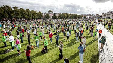 Op deze foto zijn demonstranten op het Museumplein te zien, veel hebben groene hesjes aan. Ze staan allemaal op afstand.