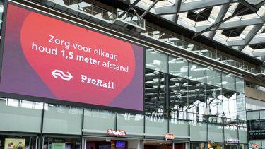 Een foto van een bord met de 1,5 meter-waarschuwing op station Den Haag Centraal