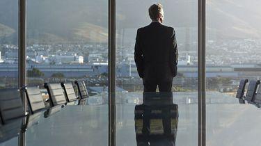 Op deze foto zie je een baas in een lege vergaderzaal staan hij staart naar buiten.