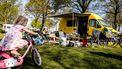 Een foto van een vrouw die in een campingstoel bij een geel kampeerbusje zit te lezen, op de voorgrond een klein meisje met een roze fiets