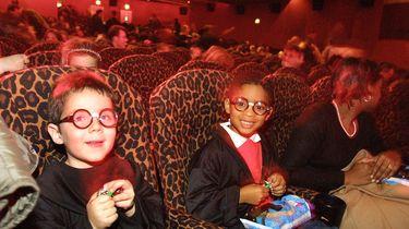 Een foto van twee kinderen met Harry Potter brilletjes in een bioscoop