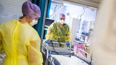 Een foto van twee zorgverleners in beschermende kleding tijden het werk op de intensive care, een rolt een nieuw bed de ruimte in.