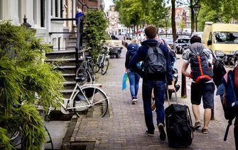 Een foto van toeristen in Amsterdam, woningeverhuurders krijgen in 2021 nieuwe regels