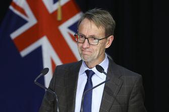 Een foto van dr. Bloomfield, achter hem hangt de Nieuw Zeelandse vlag