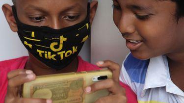 Een foto van twee jongeren die TikTok-filmpjes kijken