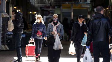 Een foto van inwoners van Rome, sommigen met een mondkapje, anderen zonder
