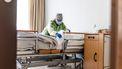 Een foto van een zorgmedewerker aan een ziekenhuisbed.