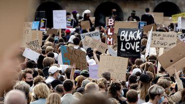 Een foto van een menigte met veel protestborden bij een demonstratie op de Dam
