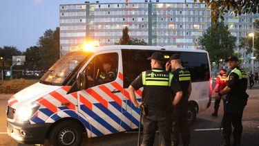 Op deze foto zijn politieagenten bij een politiebusje te zien.