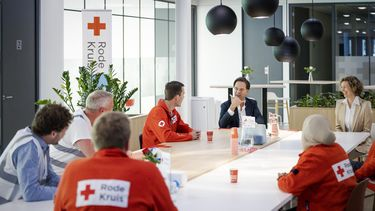 Op deze foto is Mark Rutte te zien, in gesprek met medewerkers van het Rode Kruis.