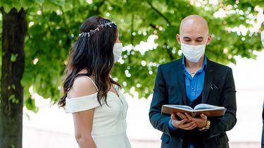 Op deze foto zie je bruid en bruidegom met een mondmasker op.