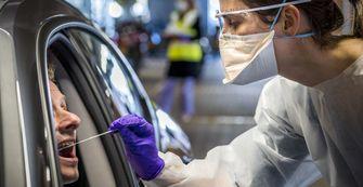 Op deze foto is een medewerker van de GGD te zien die een coronatest afneemt bij iemand in een auto.