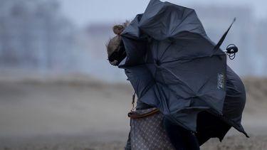 Een foto van een vrouw op het strand met een kapot gewaaide paraplu in de storm