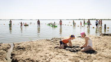Op deze foto zijn mensen te zien op een strandje, ook in het water staan mensen.