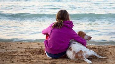 Een foto van een meisje en een hond waartegen zij vast vaak ik hou van jou zegt, op het strand