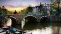 Een vrouw fiets over een brug in Amsterdam