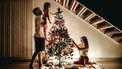 Twee mensen met hun kind bij de kerstboom.