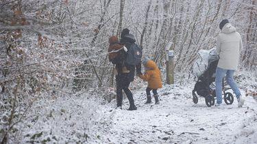 Mensen lopen in de sneeuw.