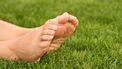 Een foto van blote voeten liggend op een grasveld. Een naakte zonnebader lag bij een treinspoor en werd aangezien voor een lijk.