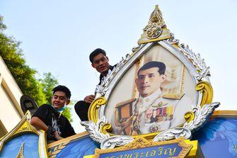 Een foto van studenten bij een portret van de koning van Thailand