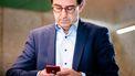 Een foto van Diederik Gommers die op zijn telefoon kijkt