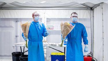 Een foto van zorgmedewerkers die coronabesmettingen opsporen en vandaag een bloemetje kregen voor hun inzet